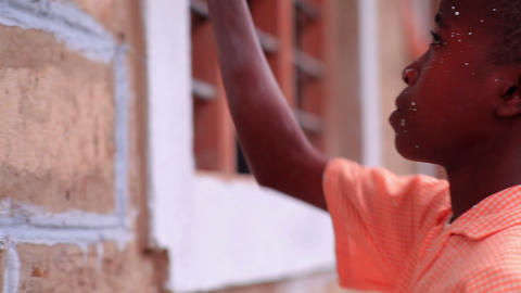 Close up of a child painting the outside of a building in Kenya Footage