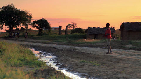 Young boy walking up a dirt road at sunset in Kenya Footage