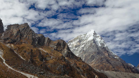 Panning shot of Time-lapse of rocky Himalayan peaks and passing clouds Footage