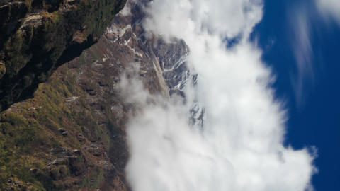 Vertical shot of Time-lapse of clouds moving around Himalayan mountains Footage