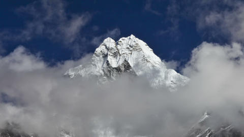 Panning shot of Time-lapse of clouds passing in front of a Himalayan peak Footage