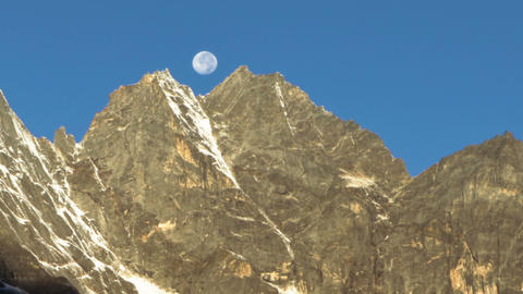 Time-lapse of the moon going behind Himalayan peaks in the morning. Cropped Footage