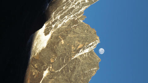 Vertical shot of Time-lapse of the moon going behind Himalayan peaks in the morn Footage