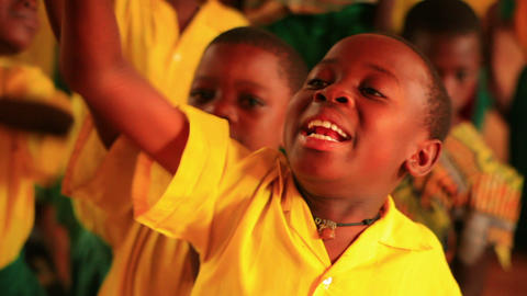 Close up of a boy raising his hand in a full classroom in Kenya Footage