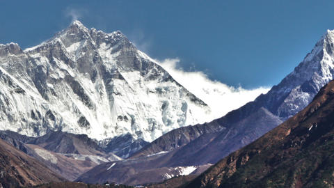 Time-lapse of the tip of Everest and surrounding peaks and trekkers on a foregro Footage