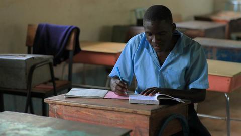 School boy doing homework in an empty classroom in a school in Kenya Footage