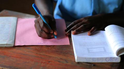 Close up of hands of a school boy doing homework in Kenya Footage