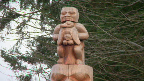 Close up of wooden figures atop a First Nations totem pole Footage