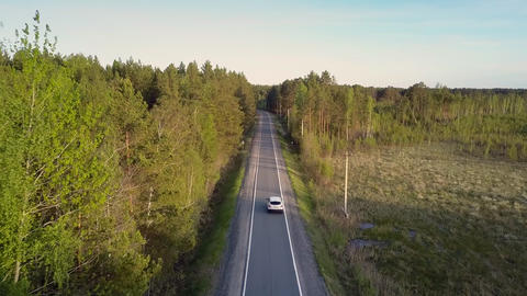 car passes by open empty plot with bushes along road Footage