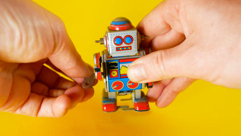 man loads a vintage metal robot to make him walk on yellow background, footage Footage