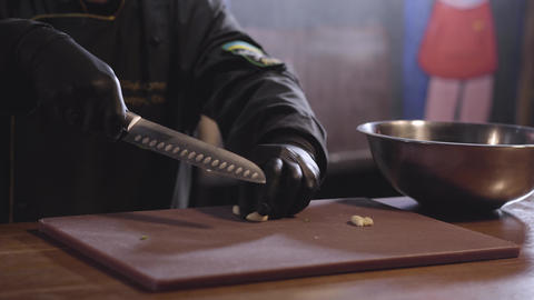 Chef crushing with sharp metal knife aromatic garlic on the wooden board to Live Action