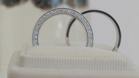 Rotating composition of two shining wedding rings . Close up macro Footage