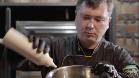 Portrait of chef in black gloves and uniform watering in the metal plate Live Action