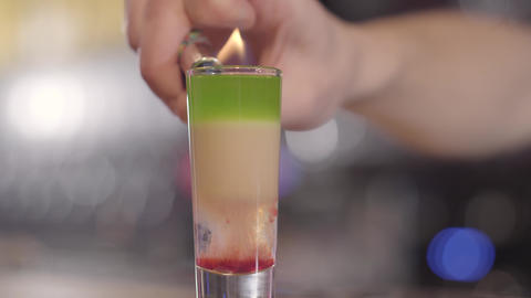 Young bartender setting fire to a refreshing alcohol cocktail into a glass with Footage