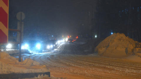 Cars passes at night along a snowy street in city Footage