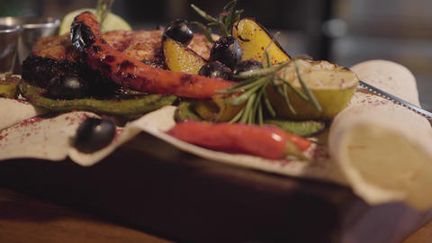 Grilled salmon fish served with herbs, olives, chili pepper, and lemon lying on Live Action