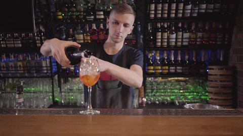 Young bartender focused on pouring a refreshing whiskey or alcohol cocktail into Footage