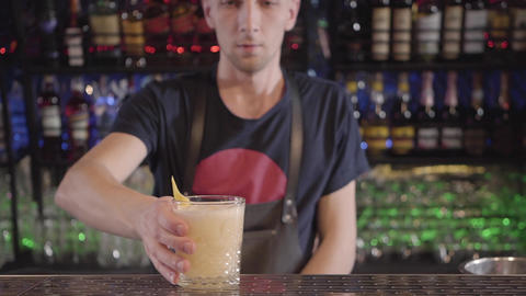 Barman prepared egg cocktail and gives it to client in glass decorated with Footage