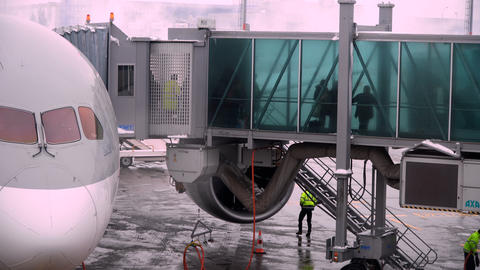 People going through jet bridge from plane to the airport Footage