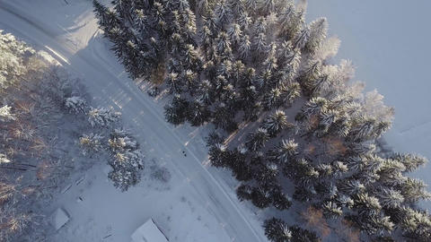 Snowy country road and two people walking in vertical aerial shot Footage