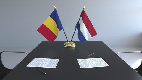 Flags of Romania and Netherlands and papers on the table. Negotiations and Footage