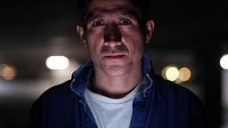 Suspicious-looking Hispanic man thinking in dark parking lot Footage