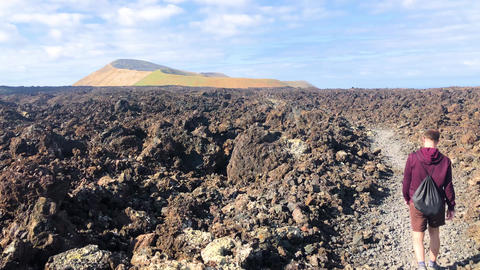 A man walking throw tourist road trail to volcano Caldera Blanca, Lanzarote Footage