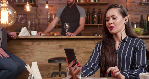 Stylish ,nice looking woman using her smartphone and headphones while engaged in Footage