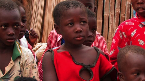 Young girl in Africa looks at someone off camera surrounded by other children Footage