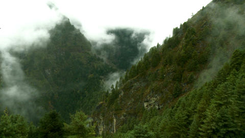 Forested mountains shrouded in mist and clouds Footage
