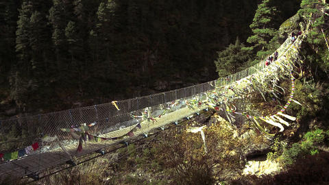 People crossing a bridge over a gorge in Nepal Footage