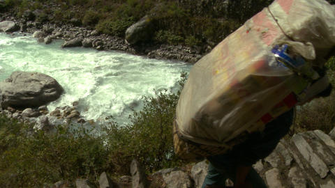 Person carrying a large pack up a rugged trail near a river in Nepal Footage