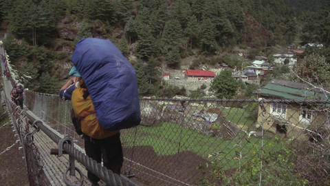 Porters and trekkers crossing a bridge in Nepal Footage