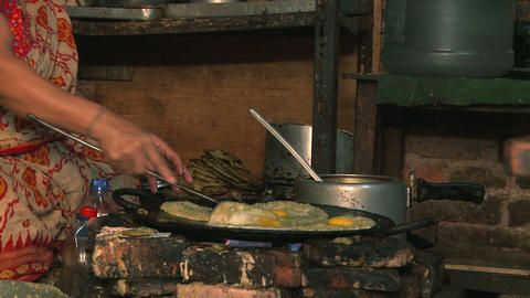 Nepali woman cooking food on a frying pan Footage