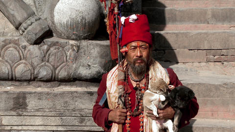 Old Nepali man holding puppies on stone steps Footage