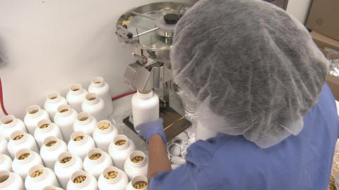 Handheld tilt shot of a woman processing capsules Footage
