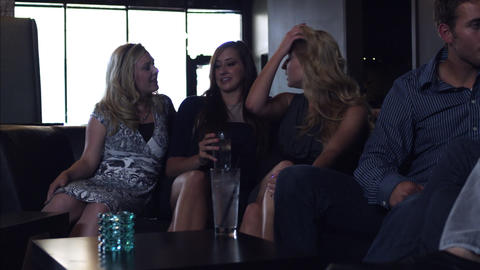 Slow motion handheld shot of three women talking and laughing together while sit Footage
