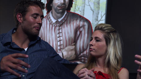 Slow handheld shot of two men and a woman talking while sitting on a couch Footage