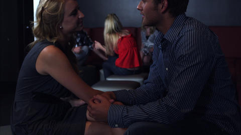 Slow motion tilt shot of a couple talking and touching each other while seated Footage