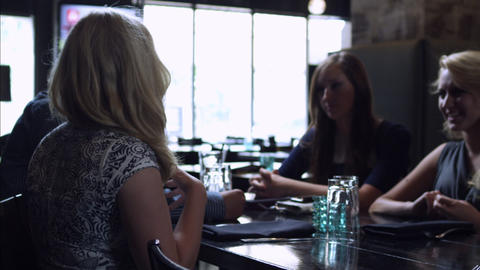 Slow motion pan of young people having a discussion at a restaurant Footage