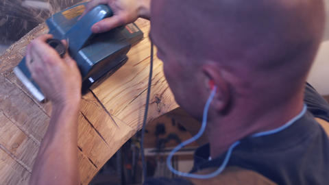 Close-up shot of a woodworker smoothing wood with an electric planer inside his  Footage