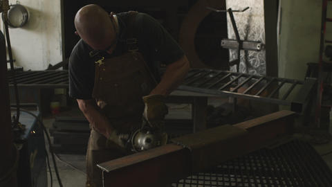 Handheld shot of man grinding metal in his workshop Live Action