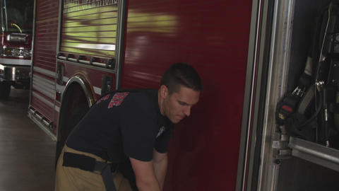 Slow motion handheld shot of fireman doing routine maintenance on fire truck in  Footage