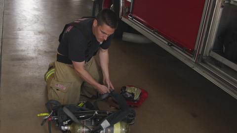 Handheld shot of fireman doing routine maintenance check on breathing apparatus  Footage