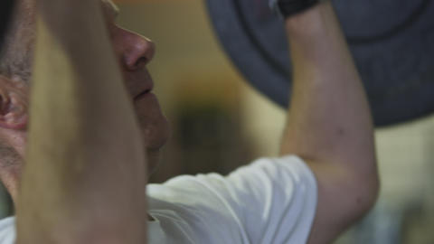 Close-up handheld shot of a man weightlifting at a gym Live Action