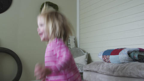 Handheld shot of a little girl as she plays and then cuddles up to her mom Footage