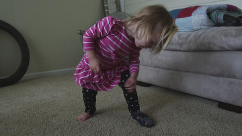 Handheld shot of a little girl trying to take off her shoe Live Action