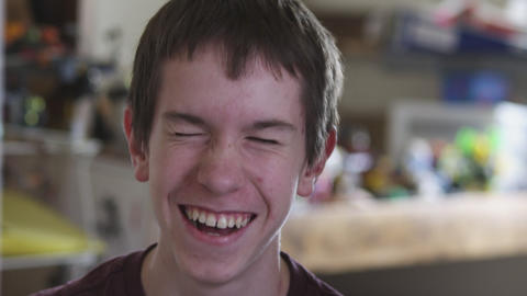 Slow motion close-up shot of a laughing nerdy boy Footage
