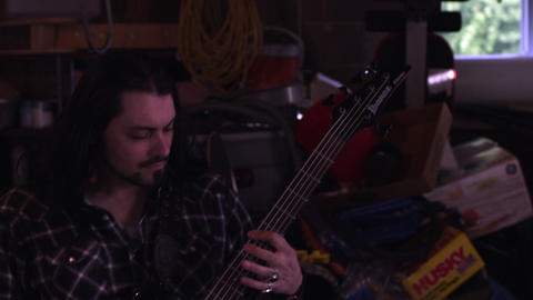 Handheld shot of a long-haired man playing a bass guitar Footage