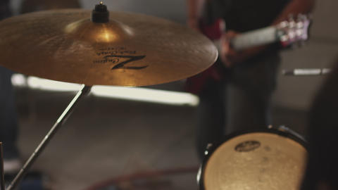Handheld shot of a drummer rehearsing with his band Footage